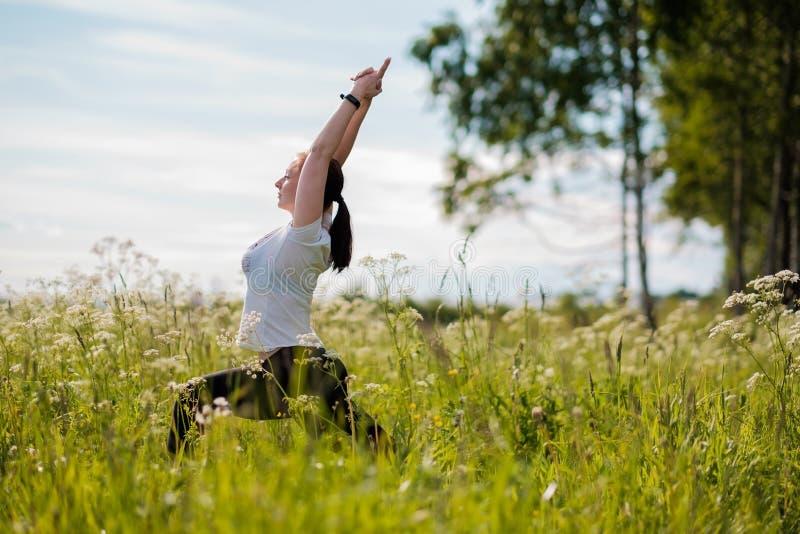 Ioga praticando da jovem mulher exterior no parque imagens de stock