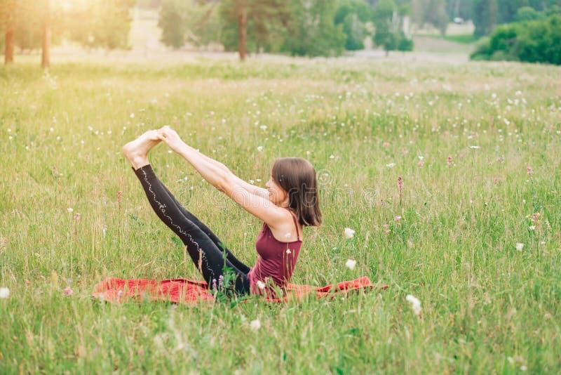 A ioga praticando da jovem mulher, faz exercícios da manhã, ginástica foto de stock