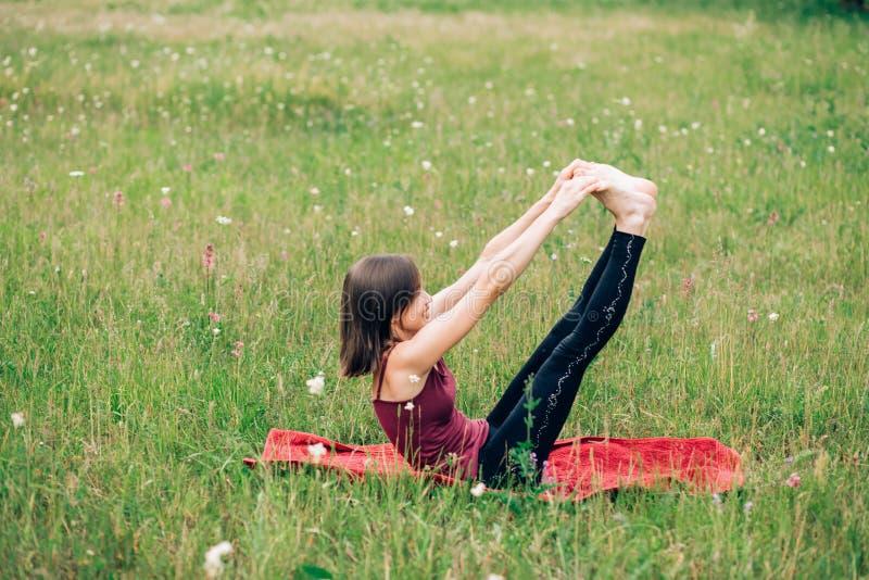 A ioga praticando da jovem mulher, faz exercícios da manhã, ginástica imagem de stock
