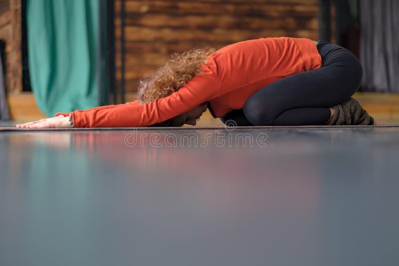 Ioga praticando da jovem mulher, fazendo o exercício da criança, pose de Balasana imagens de stock royalty free