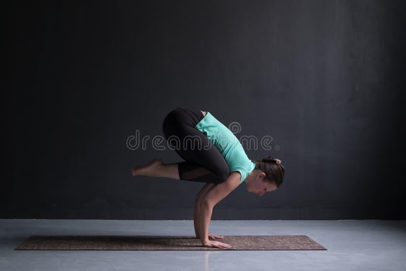 Ioga praticando da jovem mulher, fazendo o exercício do guindaste, pose de Bakasana, dando certo foto de stock royalty free
