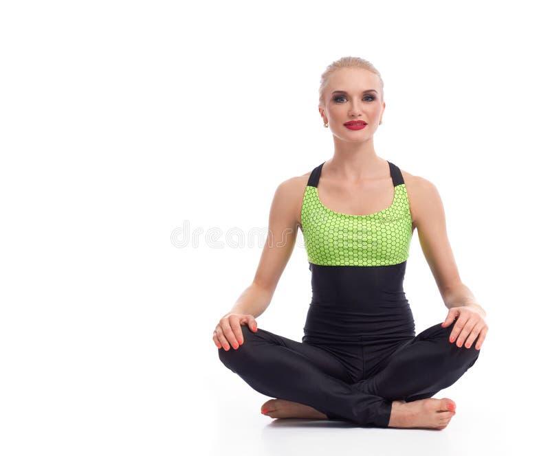 Ioga praticando da jovem mulher lindo que senta-se no assoalho fotografia de stock