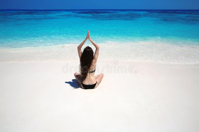 Ioga praticando da jovem mulher na praia tropical com wate azul fotos de stock royalty free