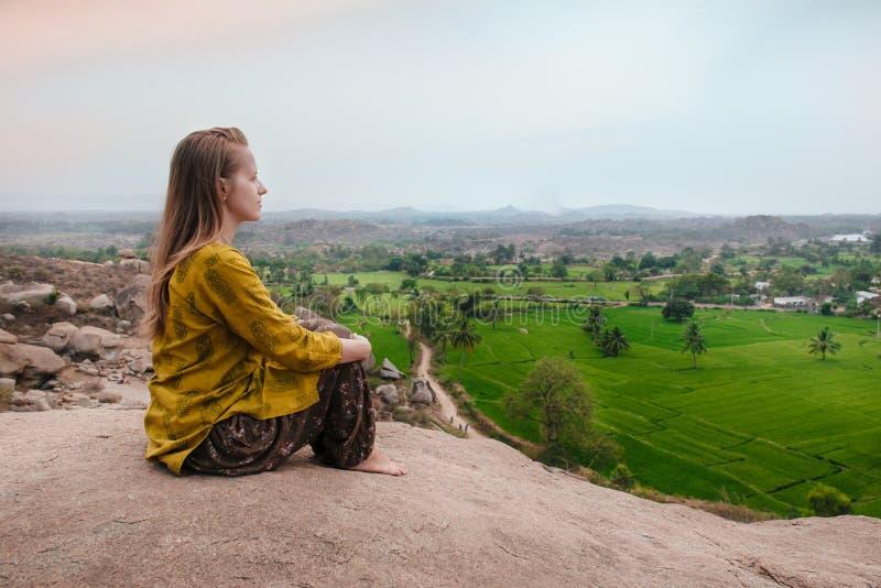 Ioga praticando da jovem mulher no penhasco da montanha no nascer do sol em Hamp imagens de stock