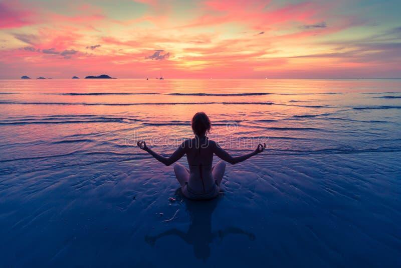 Ioga praticando da jovem mulher que senta-se na praia do mar durante um por do sol fotografia de stock royalty free