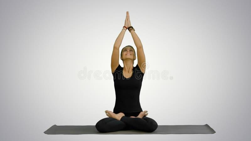 Ioga praticando da jovem mulher, sentando-se em uma posição dos lótus, meditando com os olhos fechados sobre o fundo branco foto de stock