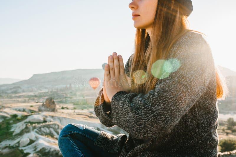 Ioga praticando da menina bonita nova na parte superior de uma montanha em Cappadocia no nascer do sol Práticas do abrandamento foto de stock