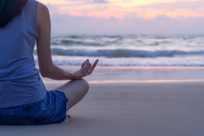Ioga praticando da mulher asiática feliz ou exercício na praia durante férias dos feriados do curso fora no oceano ou no mar da n fotos de stock