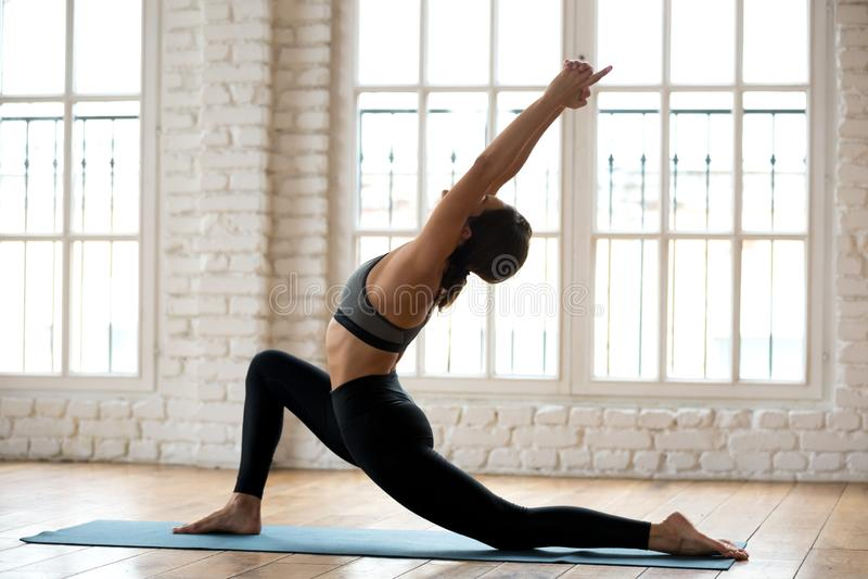 Ioga praticando da mulher atrativa nova do iogue, fazendo o anjaneyasana imagens de stock