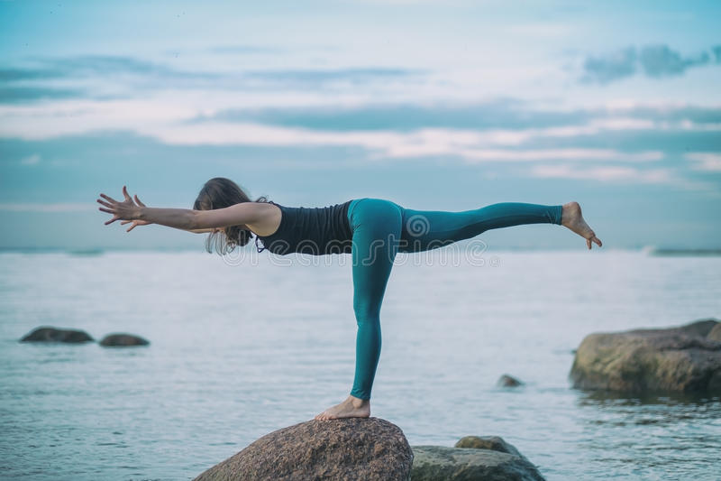 A ioga praticando da mulher atrativa nova, estando no guerreiro três exercita, pose de Virabhadrasana III foto de stock