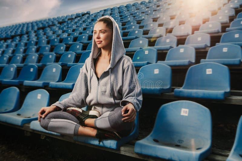 Ioga praticando da mulher atrativa nova, sentando-se no exercício de Padmasana, pose de Lotus na sessão da meditação, dando certo imagens de stock