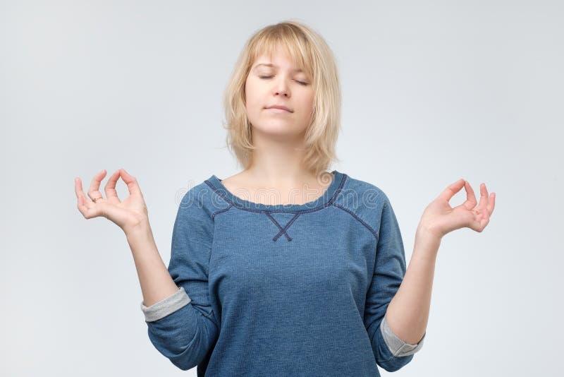 Ioga praticando da mulher calma nova do iogue, meditando com olhos fechados, relaxamento e dar certo imagens de stock