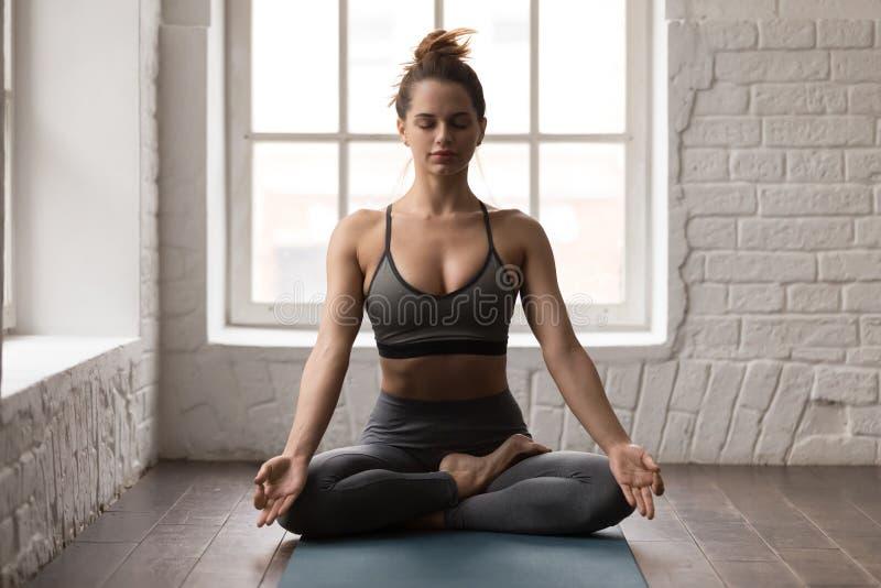 Ioga praticando da mulher calma, sentando-se na pose de Padmasana, exercício de Lotus foto de stock
