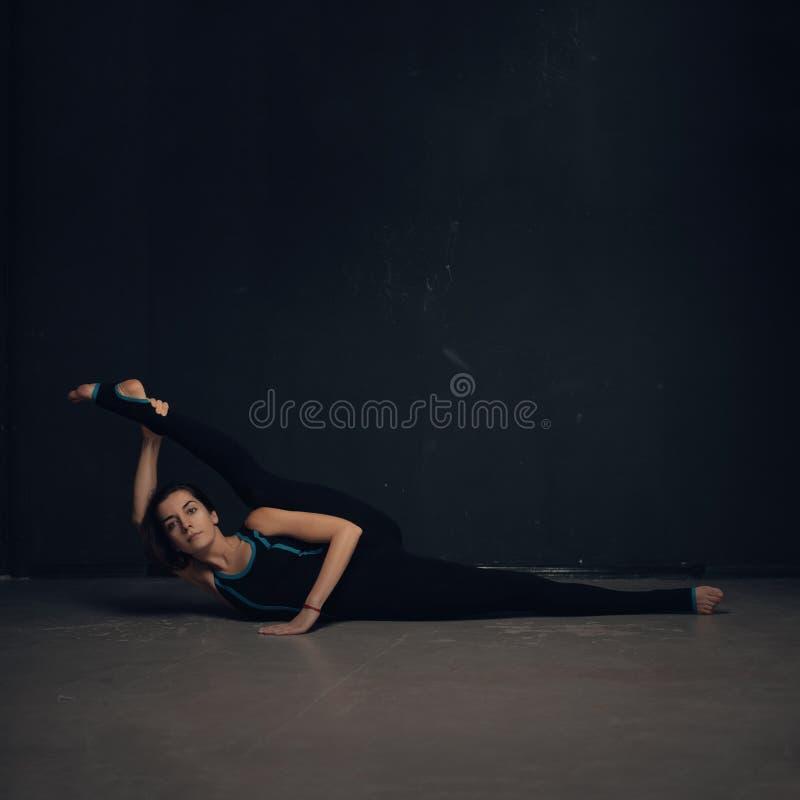 Ioga praticando da mulher contra uma parede escura imagens de stock