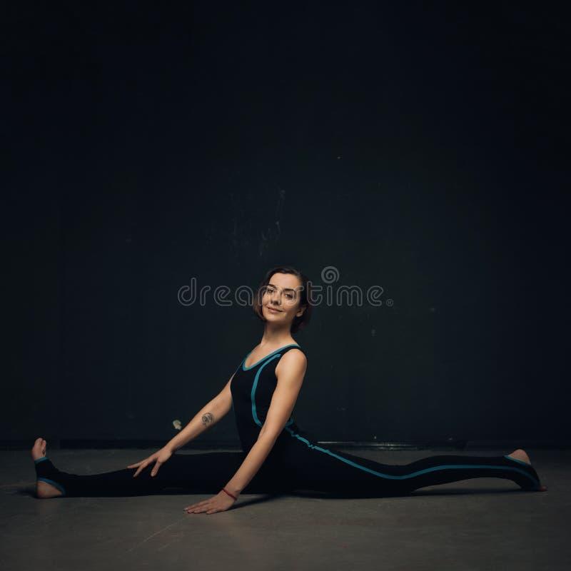 Ioga praticando da mulher contra uma parede texturized escura imagem de stock royalty free