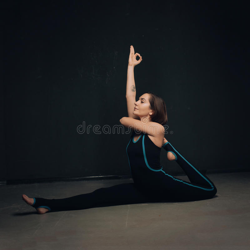 Ioga praticando da mulher contra uma parede texturized escura foto de stock royalty free