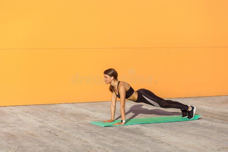 A ioga praticando da mulher desportiva nova, fazendo o impulso levanta ou a imprensa levanta o exercício, phalankasana, pose da p fotos de stock