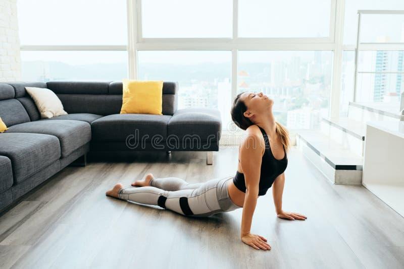 Ioga praticando da mulher em casa que faz a rotina da saudação de Sun foto de stock