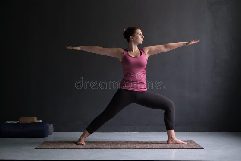 Ioga praticando da mulher, estando no exercício do guerreiro dois, pose de Virabhadrasana II imagem de stock