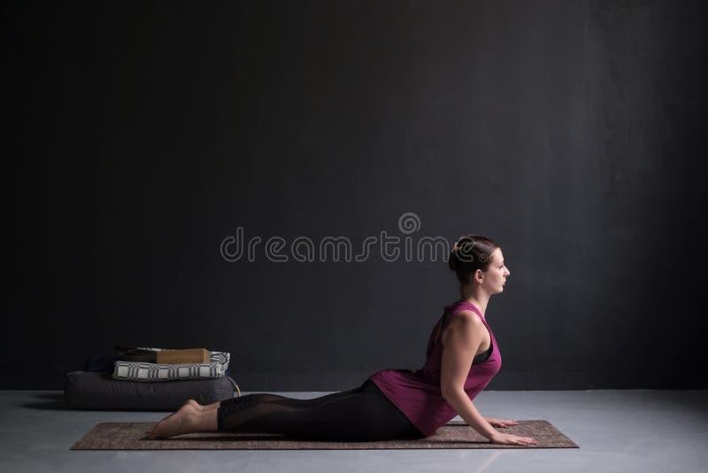Ioga praticando da mulher, fazendo o exercício da cobra, pose de Bhujangasana foto de stock