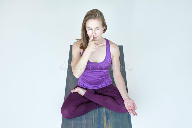 Ioga praticando da mulher, fazendo o exercício dos lótus, pranayama de respiração do shodhana do nadi foto de stock royalty free