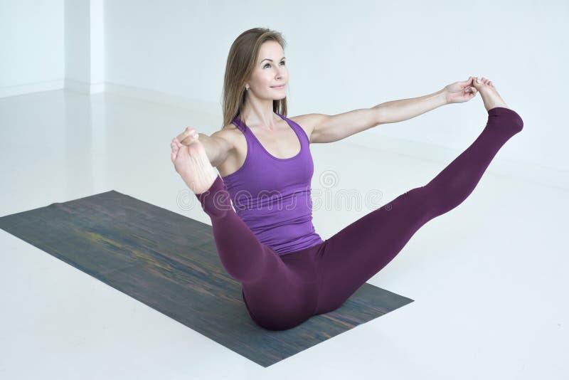 Ioga praticando da mulher, fazendo o exercício equipado com pernas largo do barco, pose de Prasarita Navasana imagens de stock royalty free