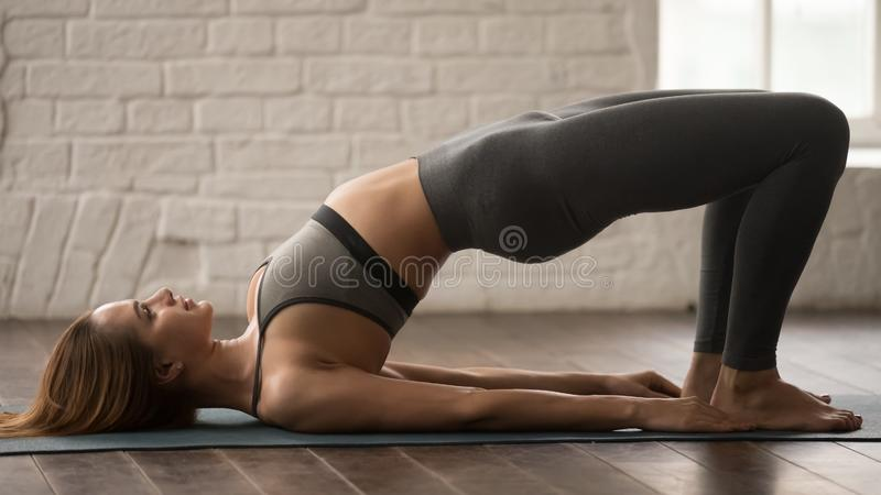 Ioga praticando da mulher, fazendo o exercício da ponte de Glute, pithasana do pada do dvi foto de stock royalty free