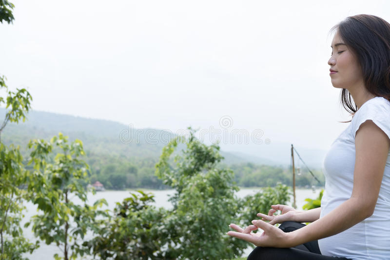 ioga praticando da mulher gravida asiática ao sentar-se no posi dos lótus fotografia de stock