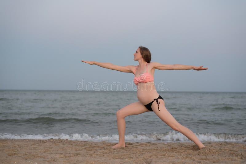 Ioga praticando da mulher gravida na praia Luz macia da noite imagens de stock royalty free