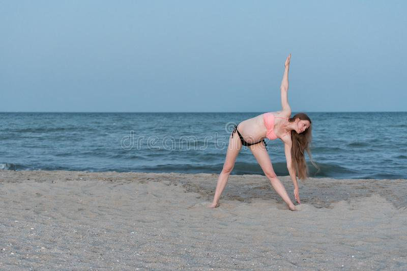 Ioga praticando da mulher gravida na praia Luz macia da noite foto de stock
