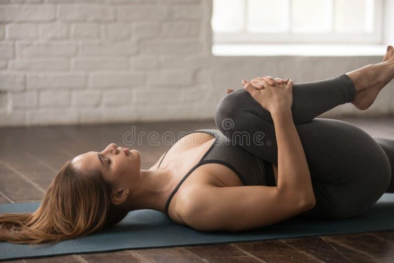 Ioga praticando da mulher, joelhos à pose da caixa, Apanasana, fim acima imagem de stock