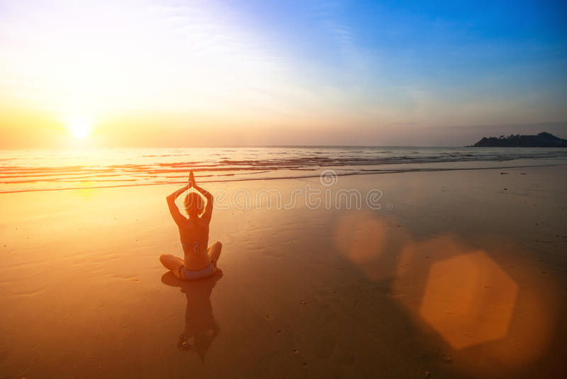 Ioga praticando da mulher na praia do mar durante o por do sol maravilhoso fotos de stock royalty free