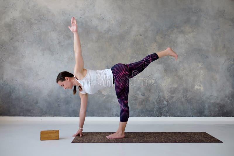 Ioga praticando da mulher no exercício torcido da meia lua, pose de Ardha Chandrasana fotografia de stock