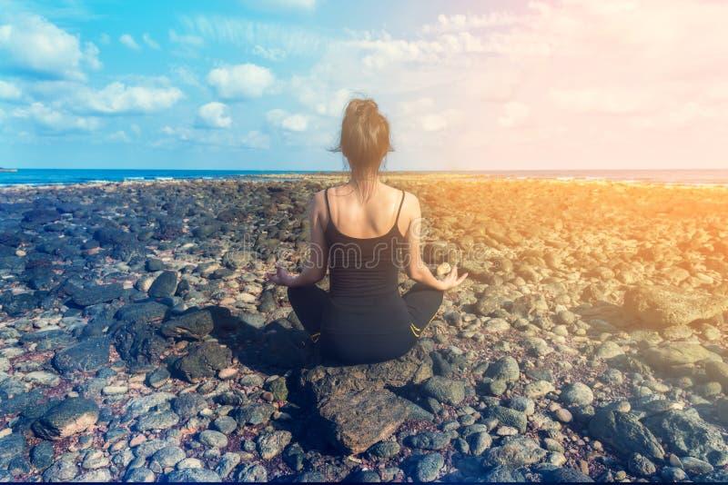 Ioga praticando da mulher saudável nova na praia foto de stock royalty free