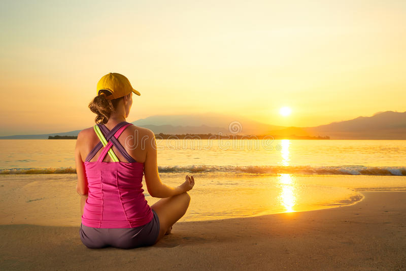 Ioga praticando da mulher saudável nova na praia no por do sol foto de stock royalty free