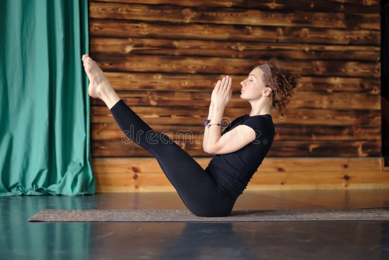 Ioga praticando da mulher, sentando-se no exercício do equilíbrio, pose de Paripurna Navasana fotos de stock