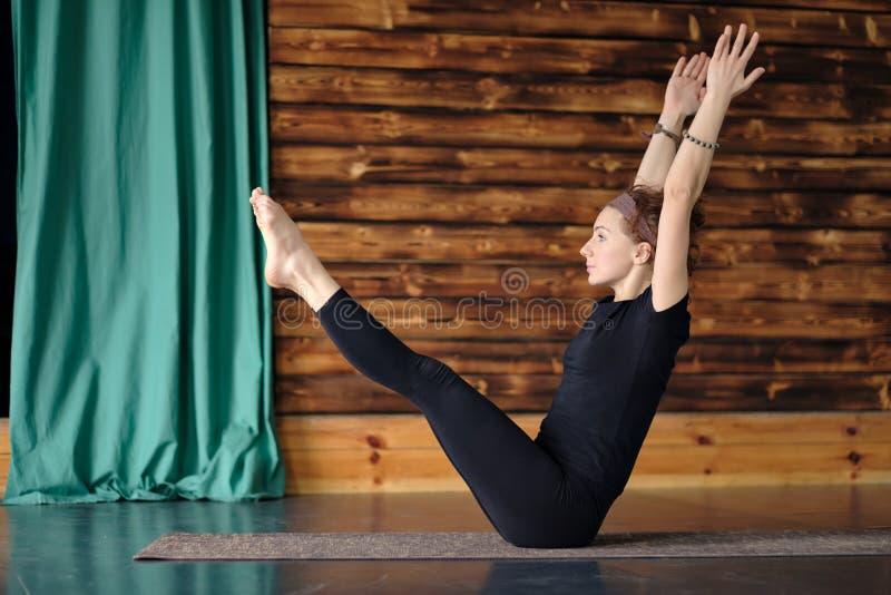 Ioga praticando da mulher, sentando-se no exercício do equilíbrio, pose de Paripurna Navasana foto de stock royalty free