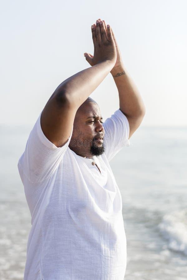 Ioga praticando do homem afro-americano na praia imagens de stock royalty free