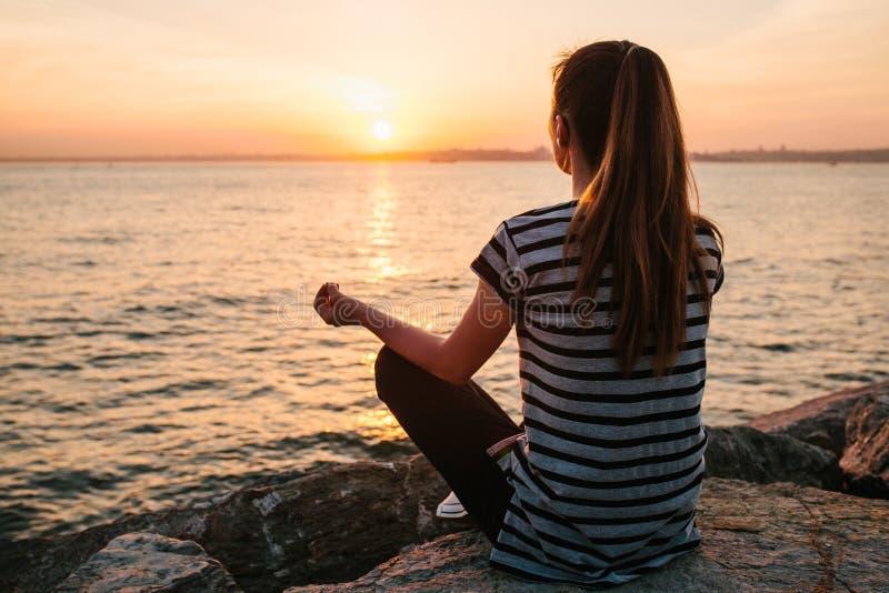 Ioga praticando e meditação da menina bonita nova nas rochas ao lado do mar no por do sol esporte yoga meditation fotografia de stock royalty free