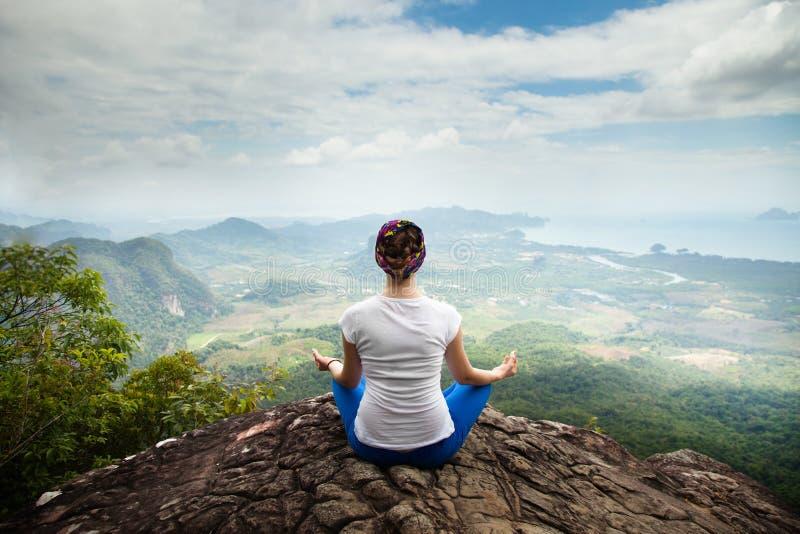 A ioga praticando e a meditação da mulher loura nova nas montanhas durante a ioga luxuosa recuam em Bali, Ásia