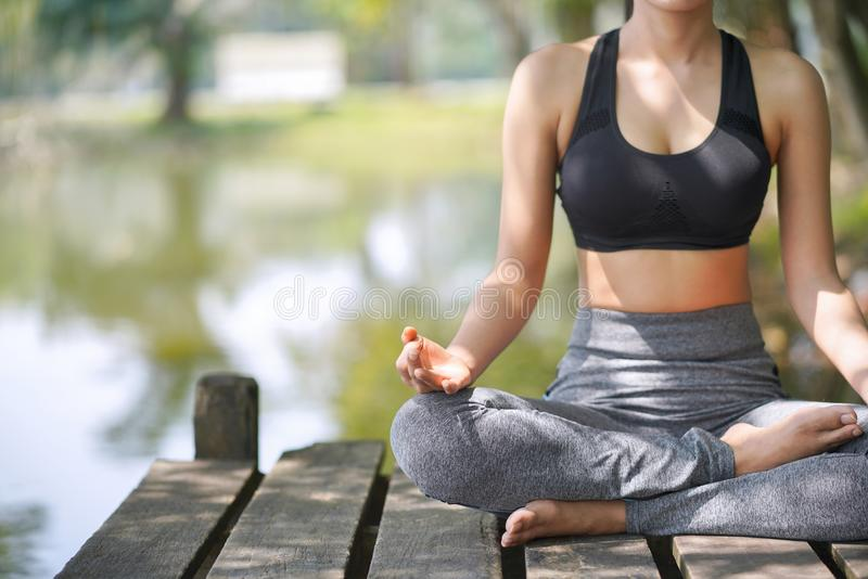 A ioga praticando na natureza, felicidade fêmea da jovem mulher, mulher asiática está praticando a ioga no lago da montanha imagem de stock