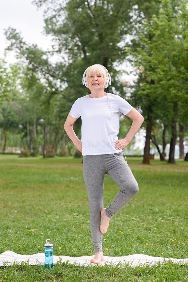 iogue fêmea superior nos fones de ouvido que praticam na esteira da ioga fotos de stock royalty free