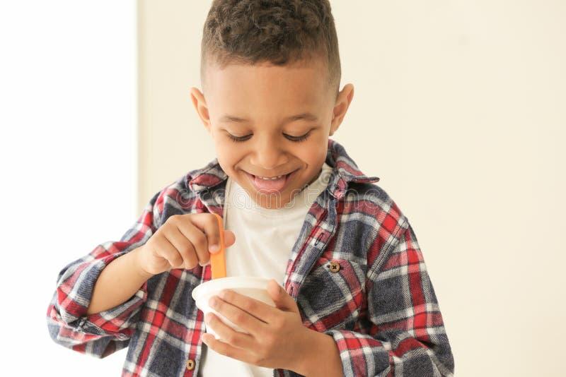 Iogurte afro-americano bonito comer do menino fotografia de stock royalty free