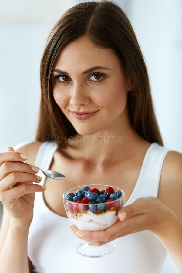 Iogurte, bagas e cereal bonitos comer da mulher Dieta saudável imagens de stock royalty free
