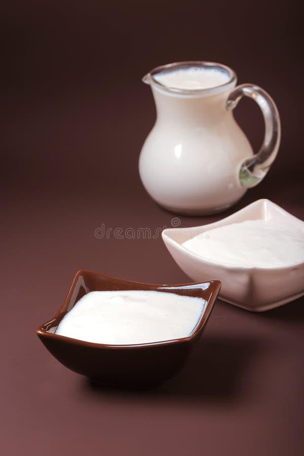 Iogurte caseiro em umas bacias quadradas cerâmicas, uma borda do jarro completamente do iogurte atrás das bacias Alimento saud foto de stock royalty free