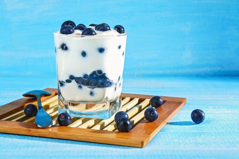 Iogurte com as bagas azuis da ameixoeira-brava em um vidro Framboesa do gelado da baga dessert imagens de stock