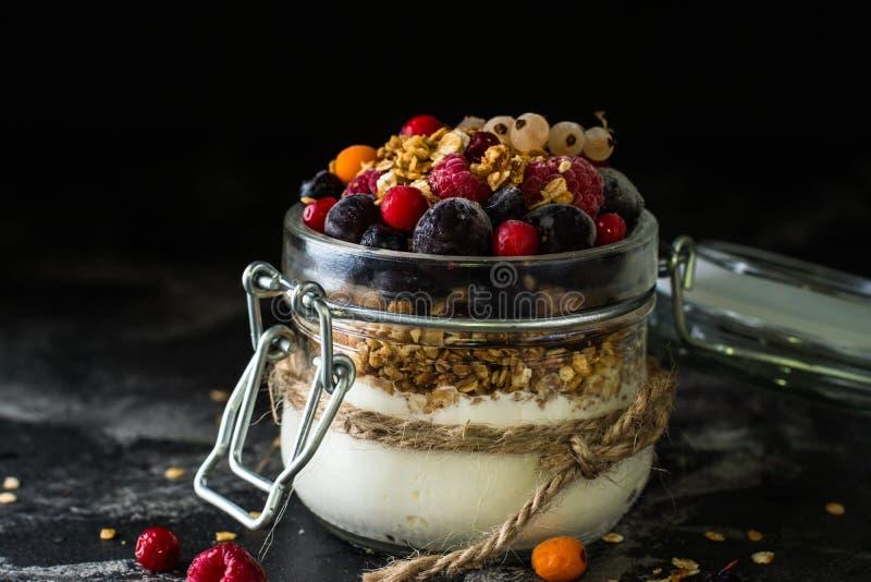 Iogurte com granola e bagas no frasco pequeno, morangos, mirtilos , corinto preto sweetness Yogurt caseiro imagens de stock