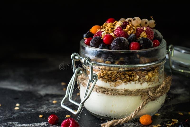 Iogurte com granola e bagas no frasco pequeno, morangos, mirtilos , corinto preto sweetness Yogurt caseiro Alimento saudável fotografia de stock