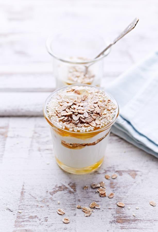 Iogurte com mel da acácia, flocos de Rye e sementes de sésamo fotografia de stock royalty free