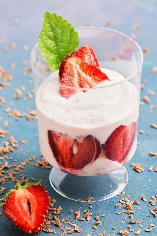 Iogurte com morangos frescas em um vidro em um fundo azul Foco seletivo Sobremesa do verão com morangos fotos de stock